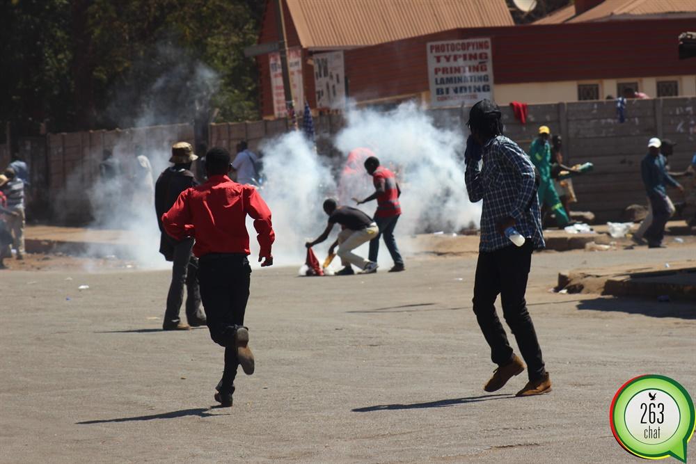 a civilian douses a detonetd tear gas canister along Mbuya Nehanda Road.-263chat