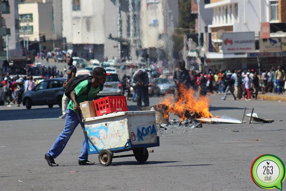 A vendor walks past burning fire , along Jason Moyo road